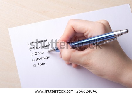 close up of female hand with pen and customer survey - stock photo
