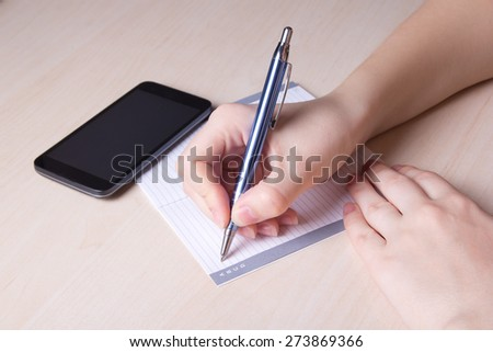 close up of female hand with pen, notebook and smart phone