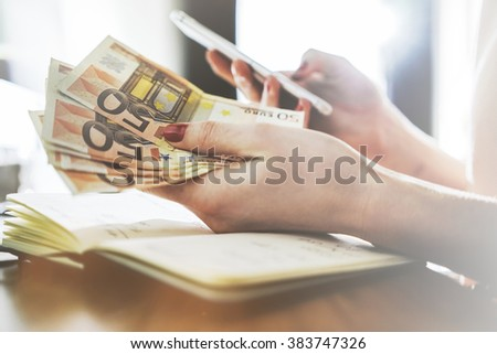 Close up of female hands counting euro bills and using smart phone, businesswoman counts money and typing on cellphone - stock photo