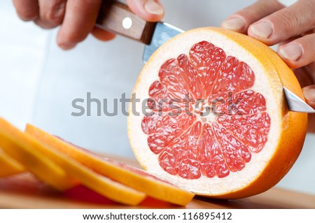 Close-up of female hands cutting a grapefruit, studio shot - stock photo
