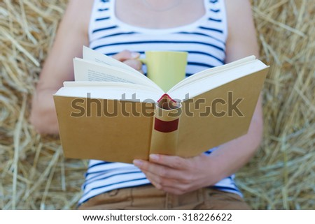 Close-up of female hands holding open book. Reading concept background - stock photo