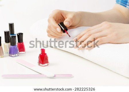 Close up of female hands making manicure - stock photo