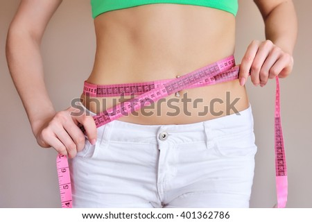 Close up of female hands measuring waist with measuring tape, dieting concept - stock photo