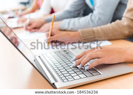 close-up of female hands on the laptop keyboard, students listen to the teacher at the University of - stock photo