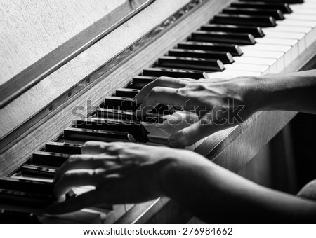 Close up of female hands playing piano, Black and White - stock photo