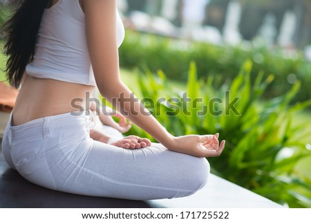 Close-up of female hands practicing yoga - stock photo