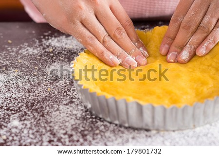 Close-up of female hands preparing tasty cake on the foreground  - stock photo