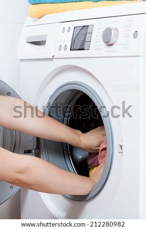 Close-up of female hands putting laundry into the washing machine drum