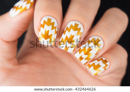 Close up of female hands showing colorful nail polish on black background. The woman is wearing golden manicure. - stock photo