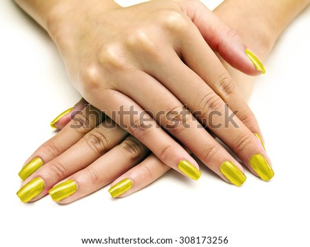 Close up of female hands showing colorful nail polish on white background.  The woman is wearing yellow manicure. - stock photo