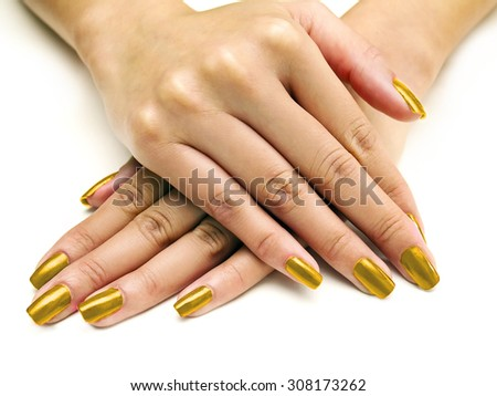 Close up of female hands showing colorful nail polish on white background.  The woman is wearing golden manicure. - stock photo