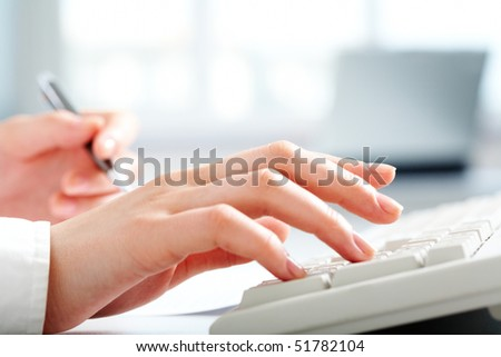 Close-up of female hands touching buttons of white keyboard and holding pen - stock photo