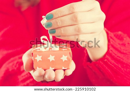 Close-up of female hands unpacking a present. A vintage image - stock photo