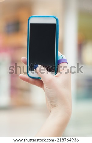 Close-up of female hands using a smart phone, in a city background.