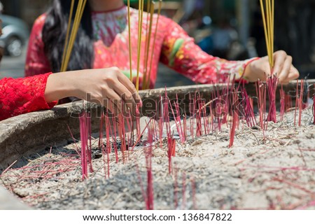 Close-up of female hands with incense sticks - stock photo