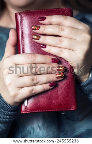 close-up of female hands with painted nail polish on the background clutch - stock photo