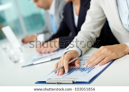 Close-up of female hands with pen over business document in working environment - stock photo