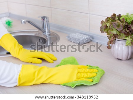 Close up of female hands with protective gloves cleaning kitchen countertop