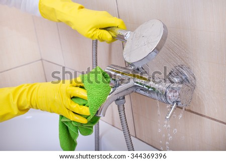 Close up of female hands with rubber gloves cleaning bathtub and faucet in the bathroom - stock photo