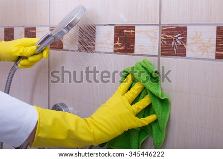 Close up of female hands with rubber gloves cleaning tiles in the bathroom - stock photo