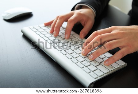 Close-up of female hands working at a keyboard/computer. Shallow DOF. - stock photo