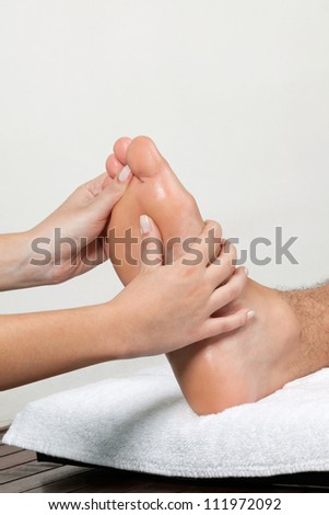 Close up of female masseuse massaging man's foot - stock photo