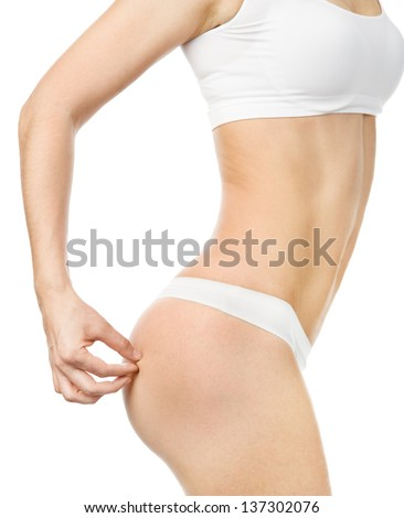 Close-up of female pinching skin of her buttocks - stock photo