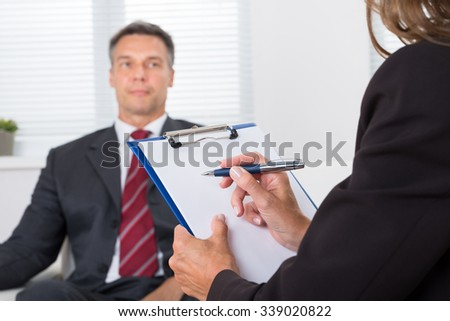Close-up Of Female Psychiatrist Writing On Clipboard In Front Of Patient - stock photo