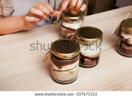 Close Up Of Females Hands Packing Dessert In A Jar - stock photo