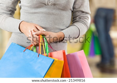 Close-up of feminine hands carrying paperbags of different colors in the mall - stock photo