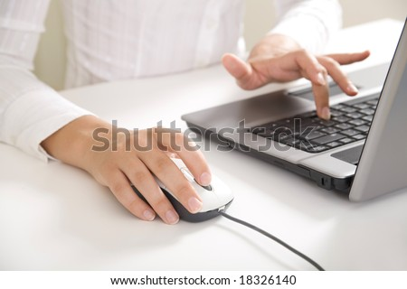 Close-up of feminine hands typing on laptop keyboard and touching mouse - stock photo