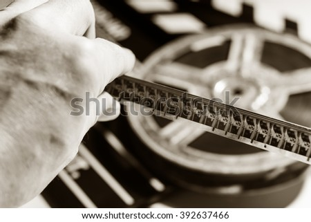Close-up of film tape in hand on background of film roll and clap cinema. View film footage - stock photo