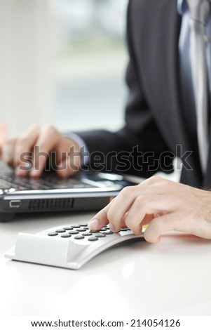 Close-up of financial advisor sitting at office and calculating data. Business people. - stock photo