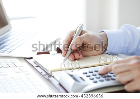 Close-up of financial businessman calculating tax expenses while sitting at office in front of computer.