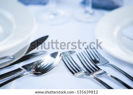 close-up of fine silver cutlery on a white set table - stock photo