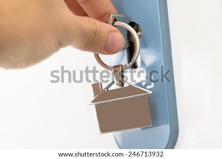 Close-up Of Finger Inserting House Key In Keyhole - stock photo