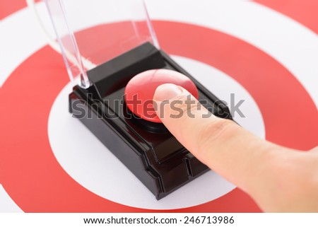 Close-up Of Finger On Red Button Over Dartboard - stock photo