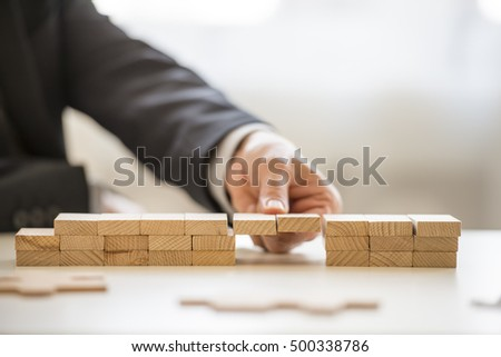 Close up of fingers from hand of business man in suit assembling a bridge made from little blocks.
