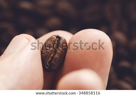 Close-up of fingers showing roasted coffee bean with blurred other coffee beans scattered behind. Shallow depth of field focused on coffee bean. Concept of individual approach to quality control. - stock photo
