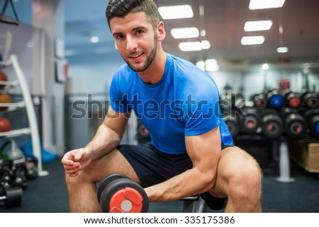 Close up of fit man working out with weights at the gym - stock photo