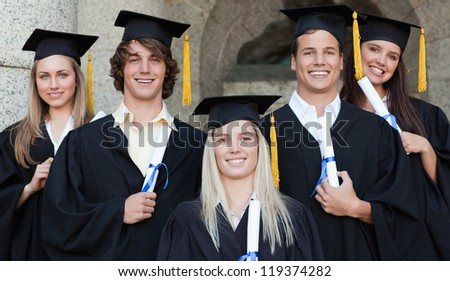 Close-up of five happy graduates posing in front of the university - stock photo
