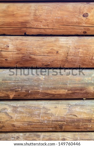 Close up of five logs that are part of a traditional log cabin wall, all in parallel and vertical. - stock photo
