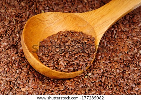 close up of flax seeds and wooden spoon as  food background  - stock photo