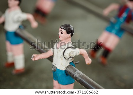 Close up of foosball table match figures. Composition of ball players of a vintage foosball table game. Color toned image. - stock photo