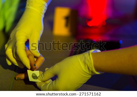 Close-up of forensic science technician taking fingerprint - stock photo