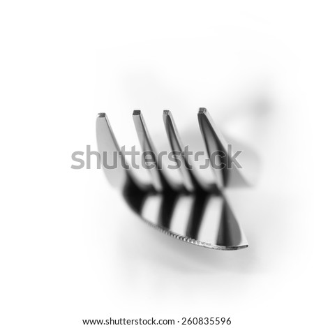 Close-up of fork and knife isolated on white background. Soft focus, shallow DOF. Focus on top of prongs. - stock photo