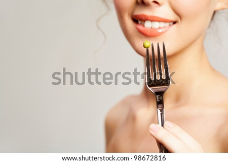 Close-up of fork with pea held by smiling girl - stock photo