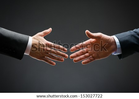 Close up of forthcoming handshake of business people. Concept of trustworthy relations and business cooperation - stock photo