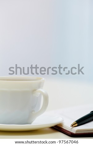 Close-up of fountain pen, notepad and cup at workplace - stock photo