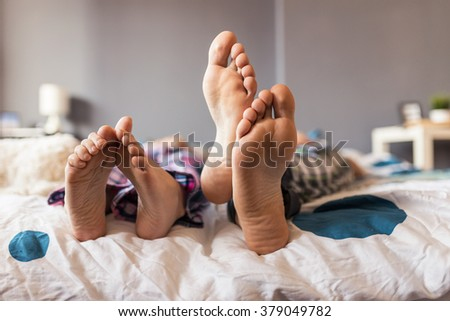 Close up of four feet in a bed. Selective focus, depth of field, focus on feet  - stock photo